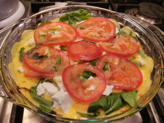 The egg mixture is poured on and topped with sliced tomatoes