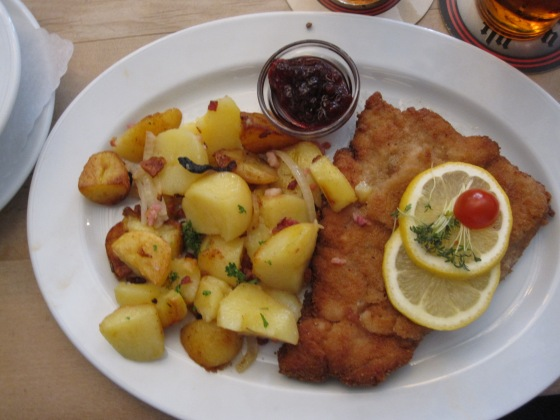"""Schnitzel Wiener Art"" (pork meat) with cranberries, fried potatoes and salad"
