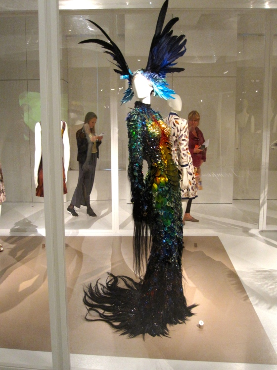Theirry Mugler, Haute Couture Autumn-Winter 1997-1998; Dress as fantastical animal skin, bodice in thermally shaped man-made scales, embellished ith ostrich feathers, sequins, rhinestones, horse hair, and bead embroidery, head dress with dyed swan and goose feathers, sequins, and beads