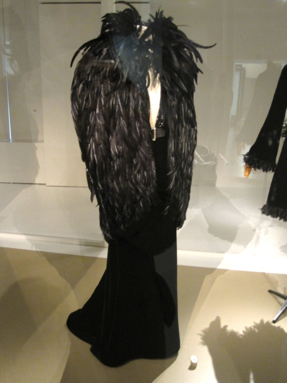 Yves Saint Laurent, Haute Couture Autumn-Winter 2000-2001; Evening ensemble of cape with rooster feathers and a dress in lacquered velvet
