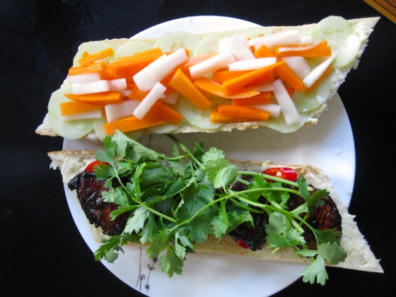 Assembled bánh mì - mayonnaise, cucumber and pickled vegetables on one side, mayonnaise, chili peppers, pork, and cilantro on the other