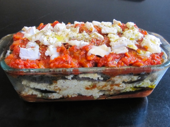 Topped with tomato sauce and goat cheese, ready to go into the oven