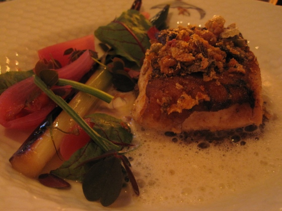 Grilled hake on top of mushrooms with pickled red onion, rose petals, grilled leek, and fried cod skin and pork rinds